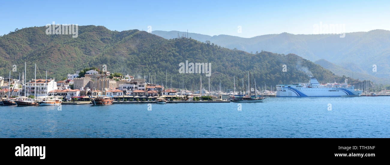 Yachts and boats in port near city with castle - Stock Image