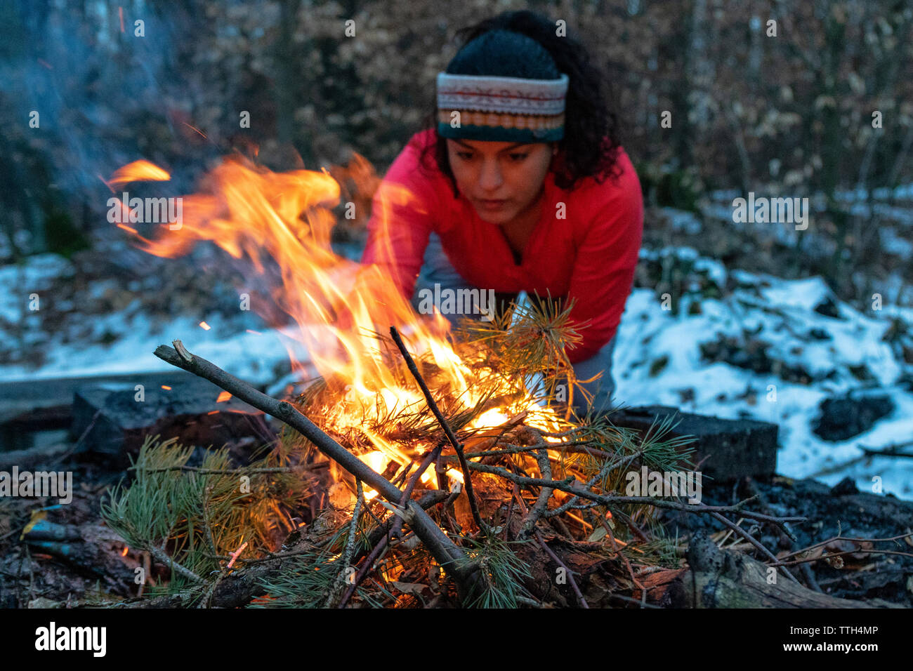 Woman Starting A Bonfire At A Fireplace In The Forest In Autumn