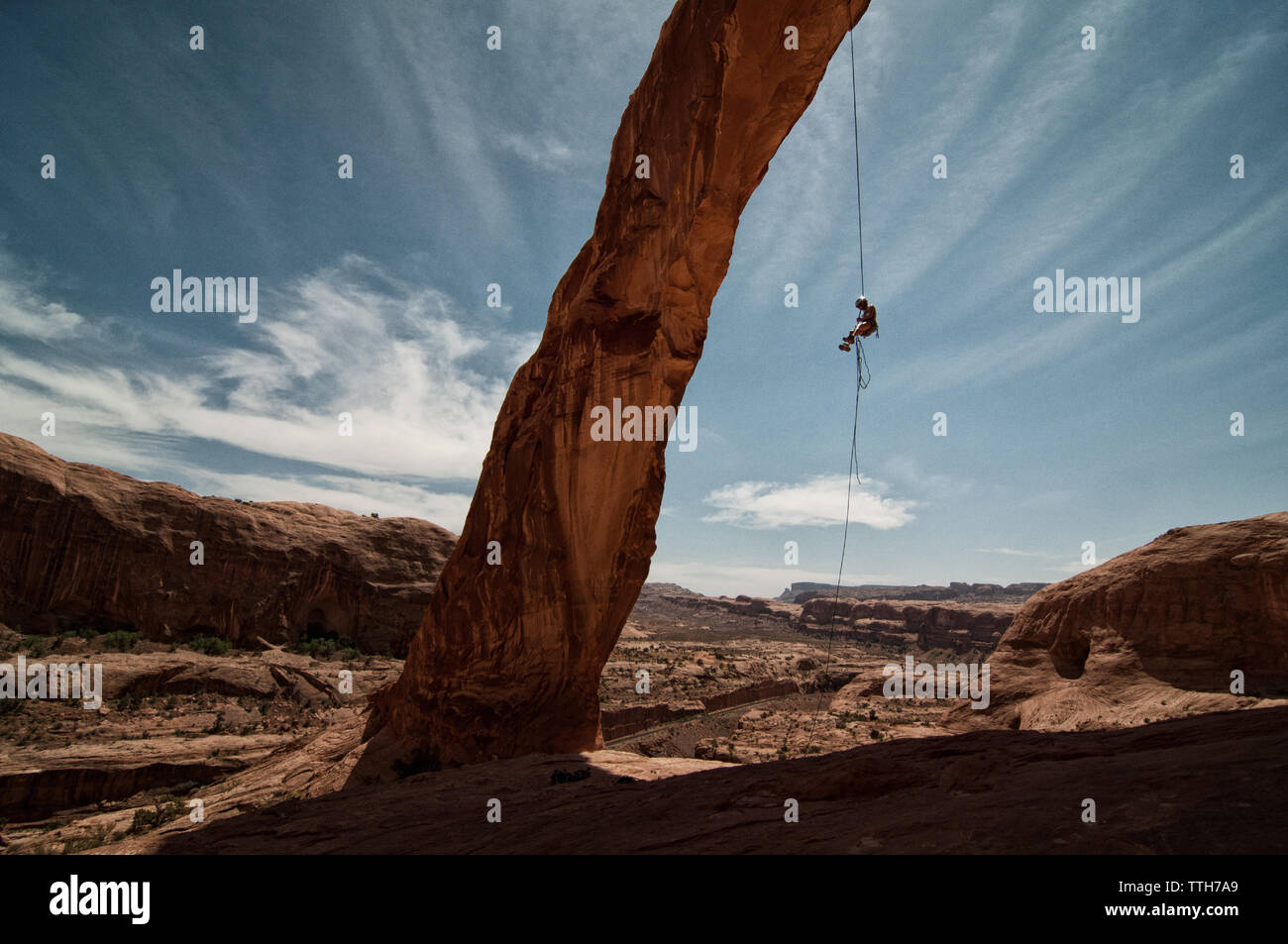 Landscape image of figure rappelling down Corona Arch - Stock Image