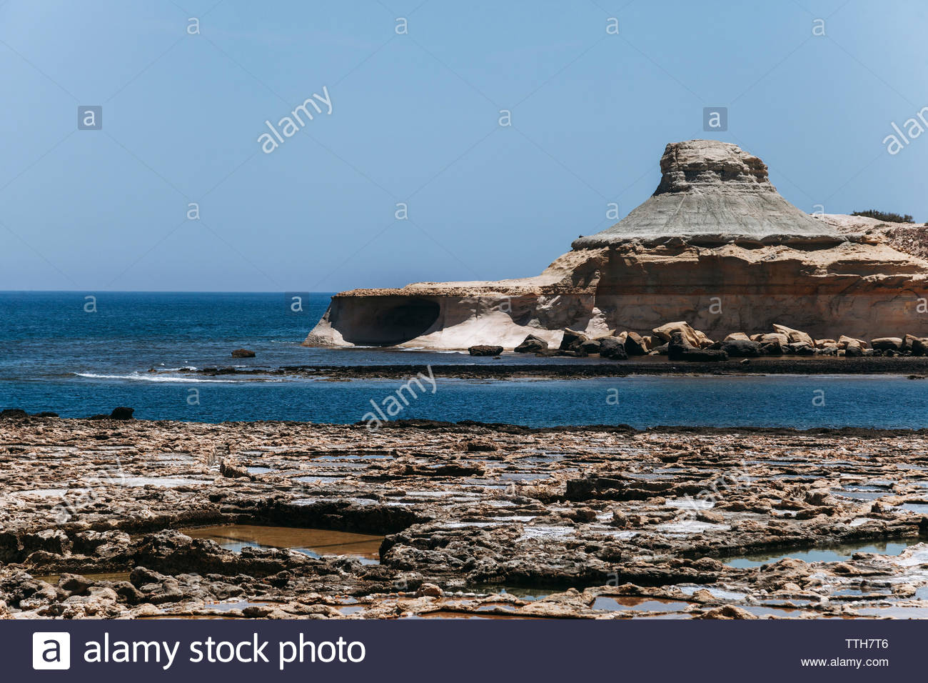 Rock formations and salt flat at coastline by sea against sky during sunny day - Stock Image