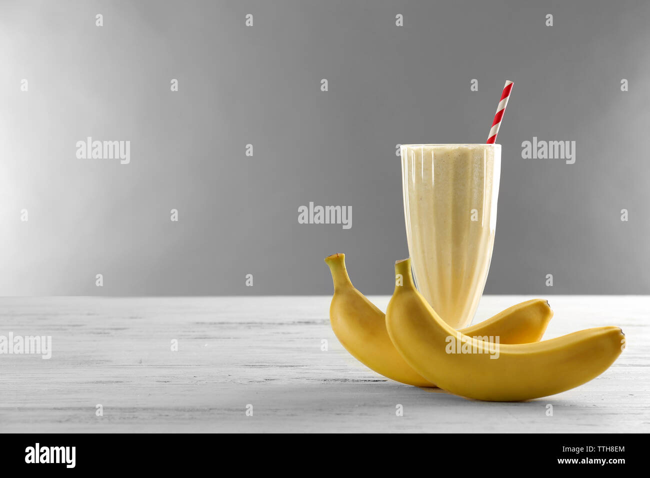 Glass of milk cocktail with bananas on grey background - Stock Image