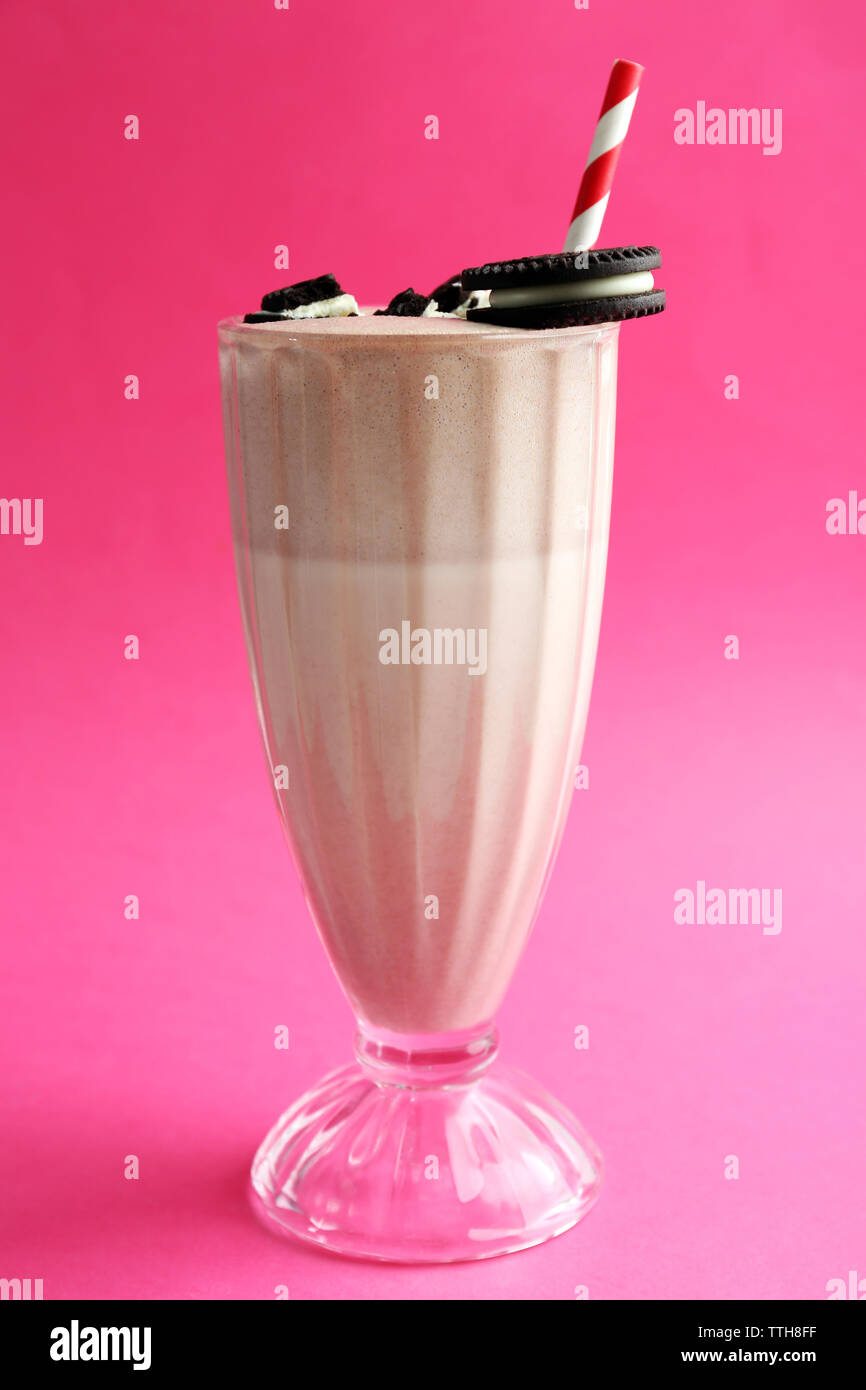 Glass of milk cocktail with chocolate cookies on pink background - Stock Image