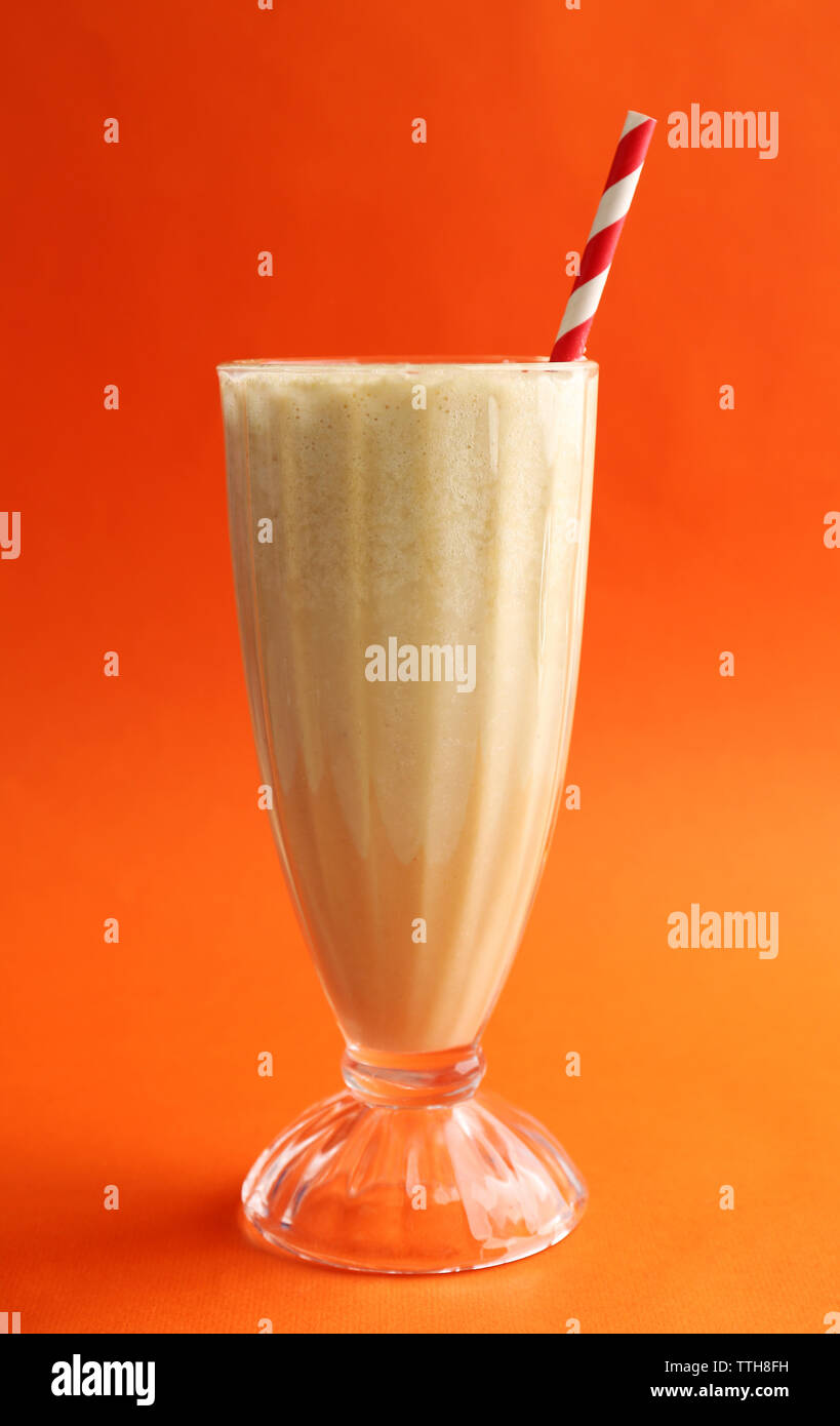 Glass of milk cocktail on orange background - Stock Image