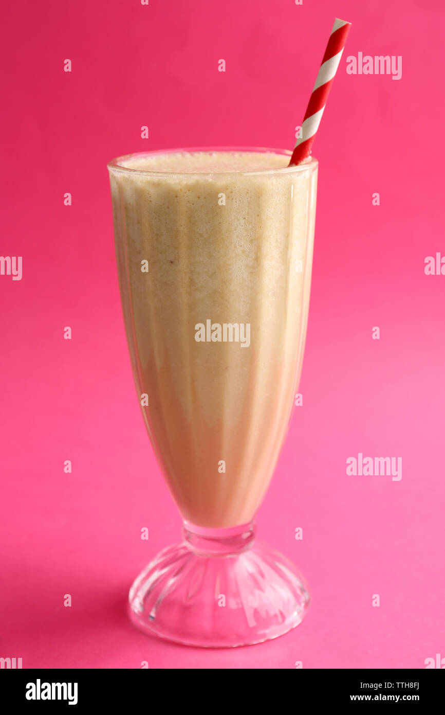 Glass of milk cocktail on pink background - Stock Image