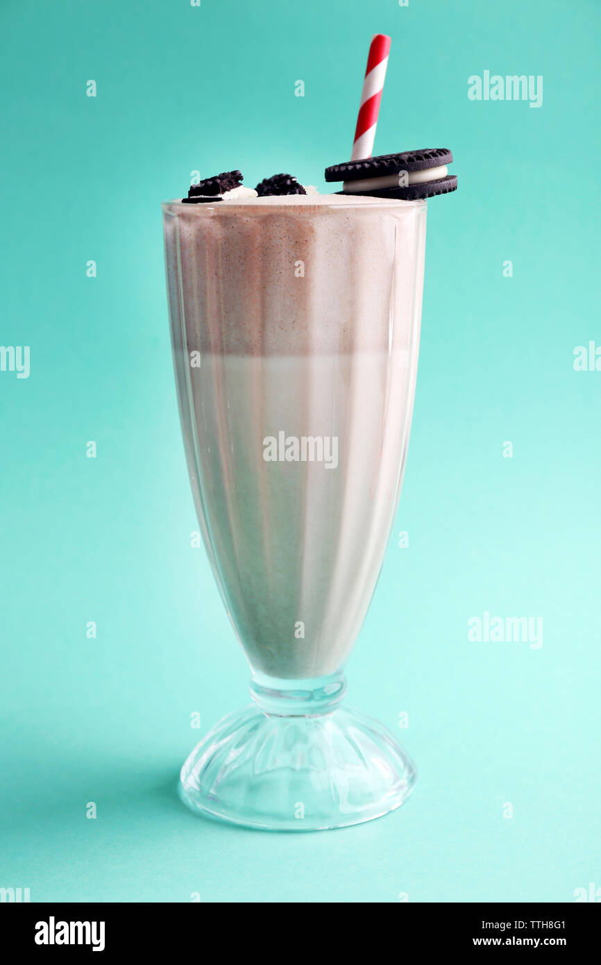 Glass of milk cocktail with chocolate cookies on turquoise background - Stock Image
