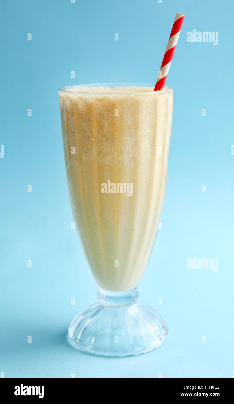 Glass of milk cocktail on blue background - Stock Image