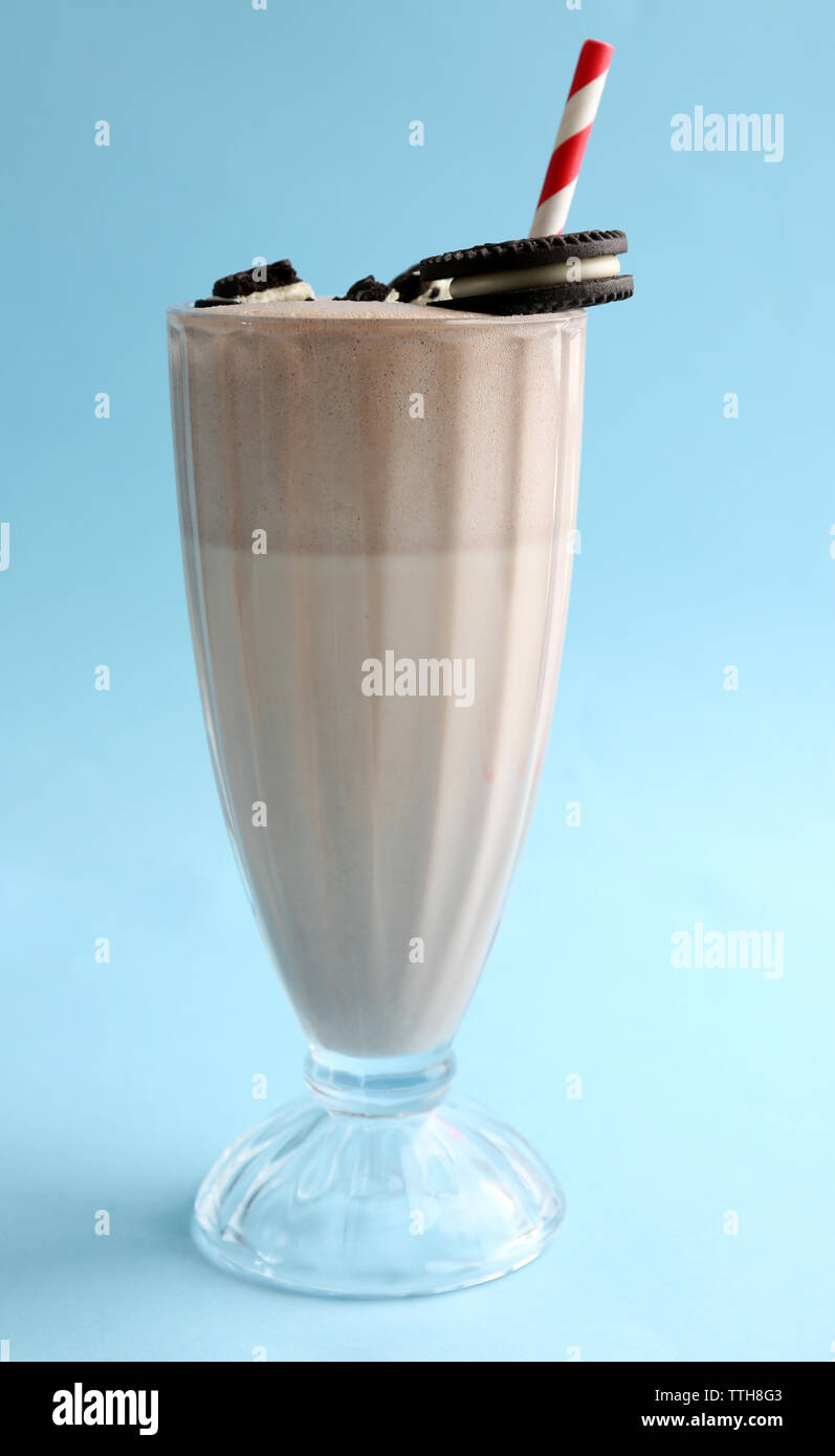 Glass of milk cocktail with chocolate cookies on blue background - Stock Image