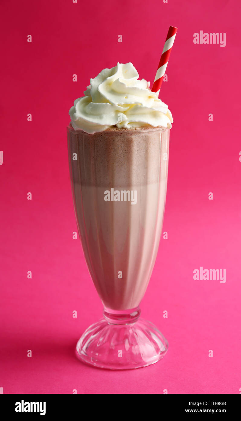 Glass of milk cocktail with cream on pink background - Stock Image