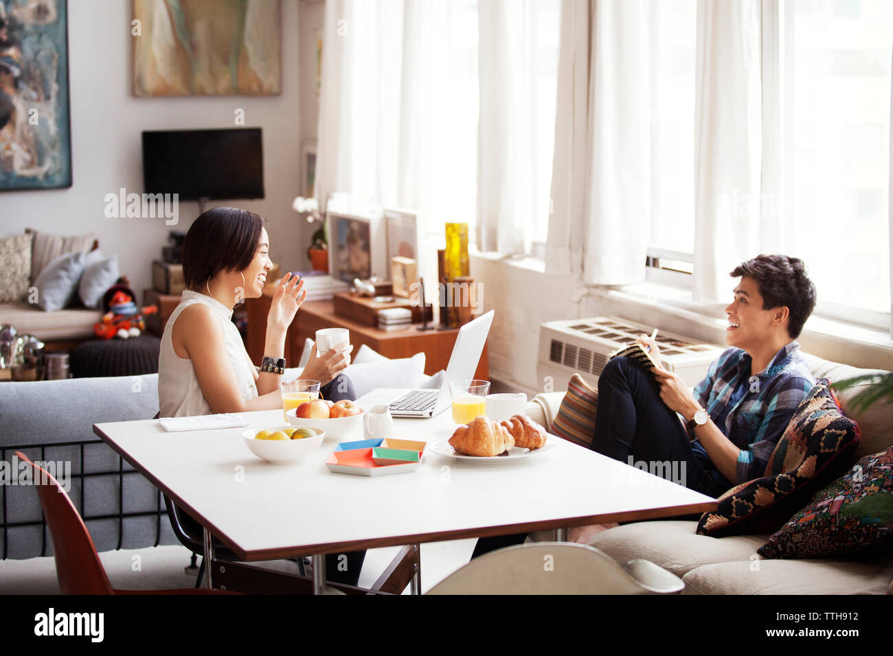 Cheerful couple spending leisure time in living room - Stock Image