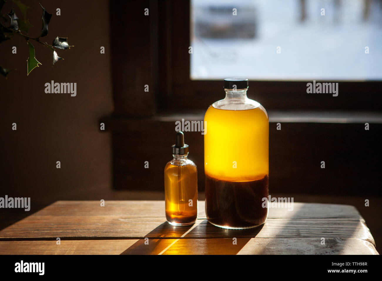 Oil bottles on wooden table at home - Stock Image