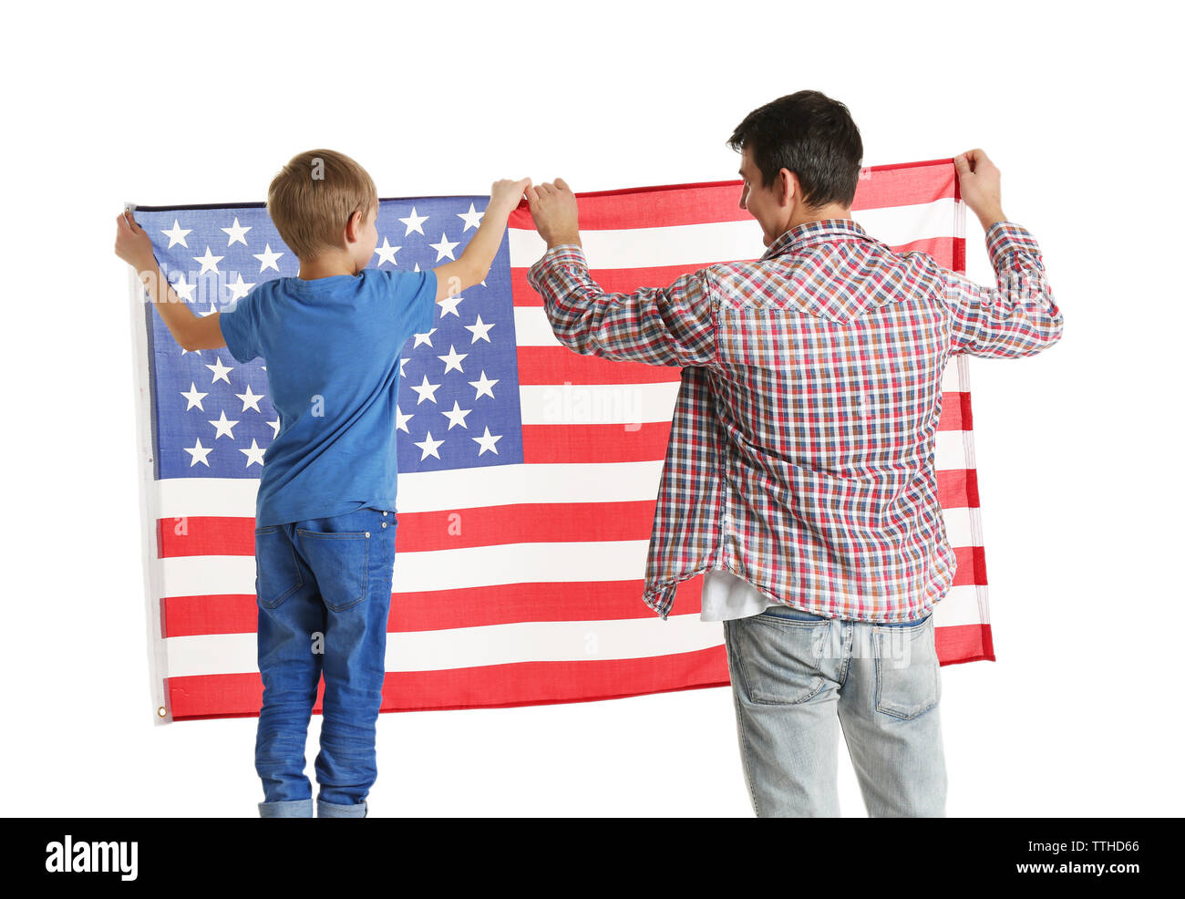 Father and his son hanging   USA flag on the white wall - Stock Image