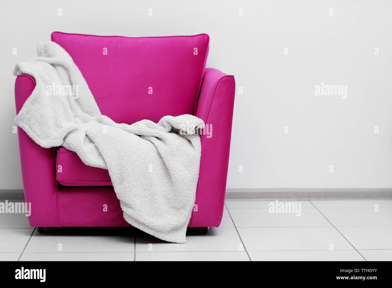 pink armchair with blanket on light wall background TTHDYY