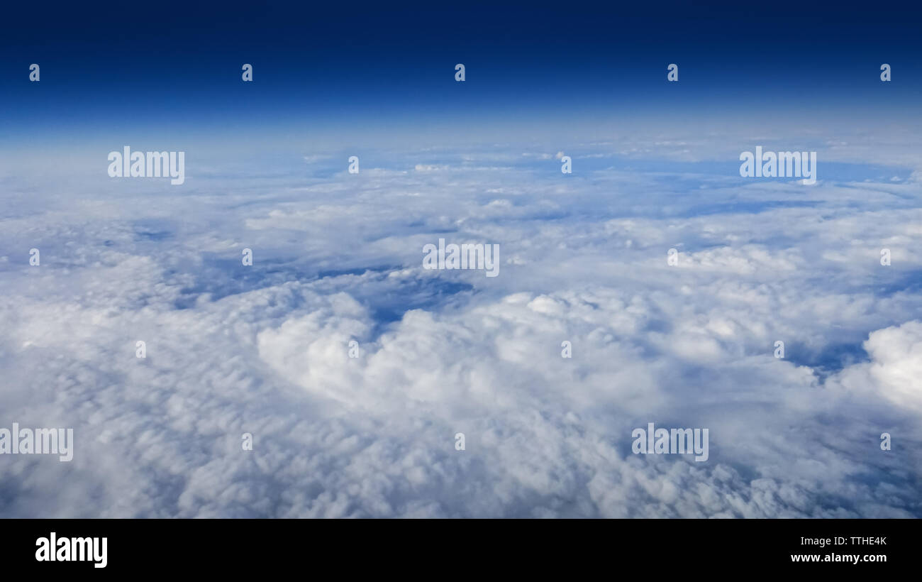 The beautiful cloudscape with clear blue sky. Panorama above white clouds as seen through window of an aircraft. A view from airplane. Stock Photo