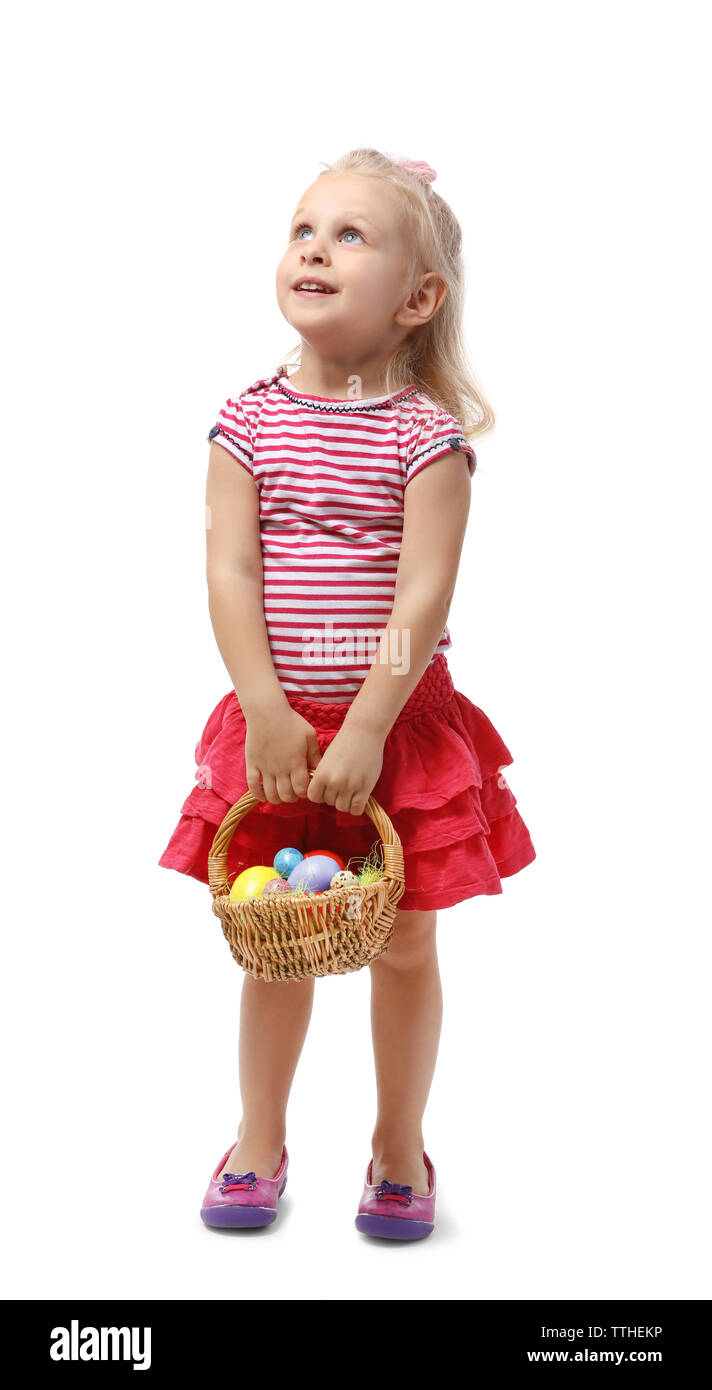 Little girl holing wicker basket with Easter eggs isolated on white - Stock Image