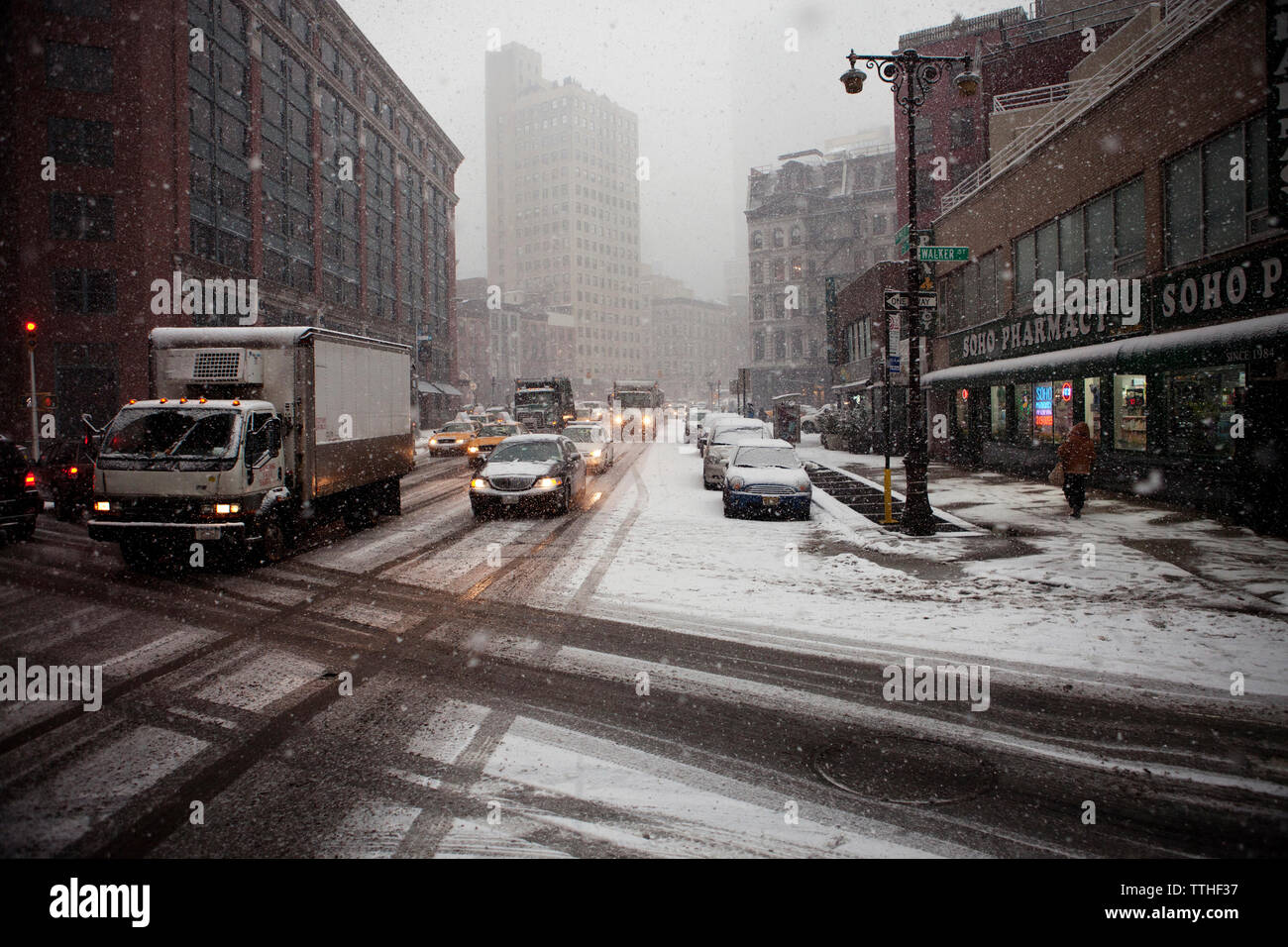 Vehicles on road amidst buildings in city during snowfall - Stock Image