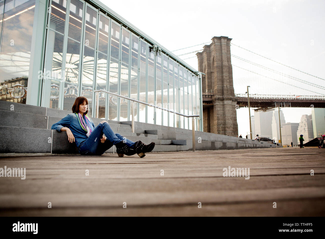 Thoughtful woman sitting by Jane's Carousel against Brooklyn Bridge - Stock Image