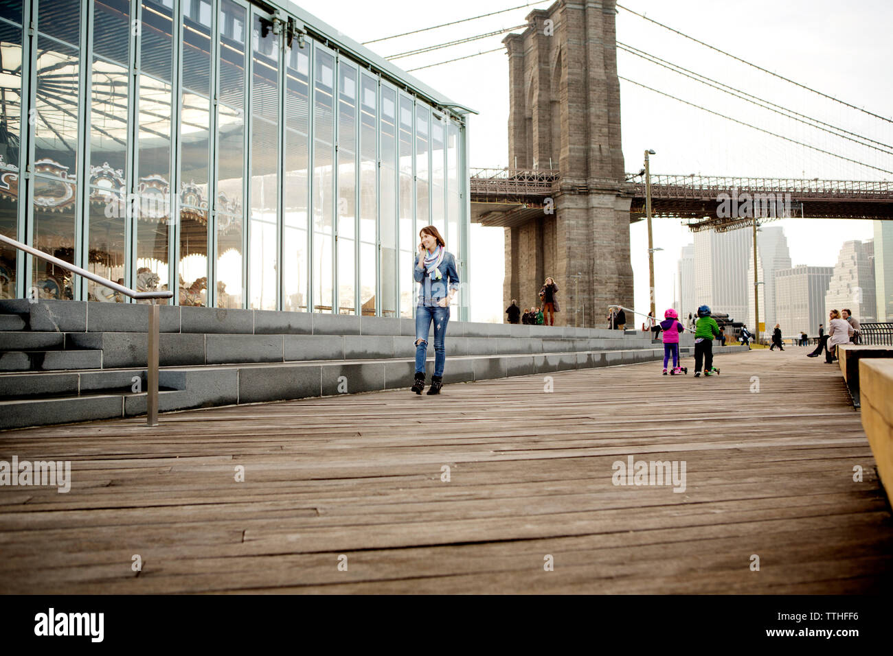 Woman using phone while walking by Jane's Carousel against Brooklyn Bridge - Stock Image