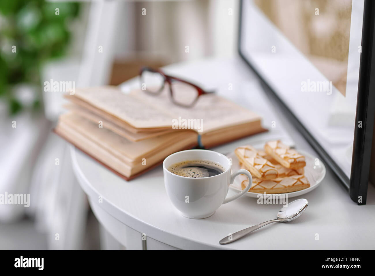 White cup of the coffee on the table  in a light room.. - Stock Image