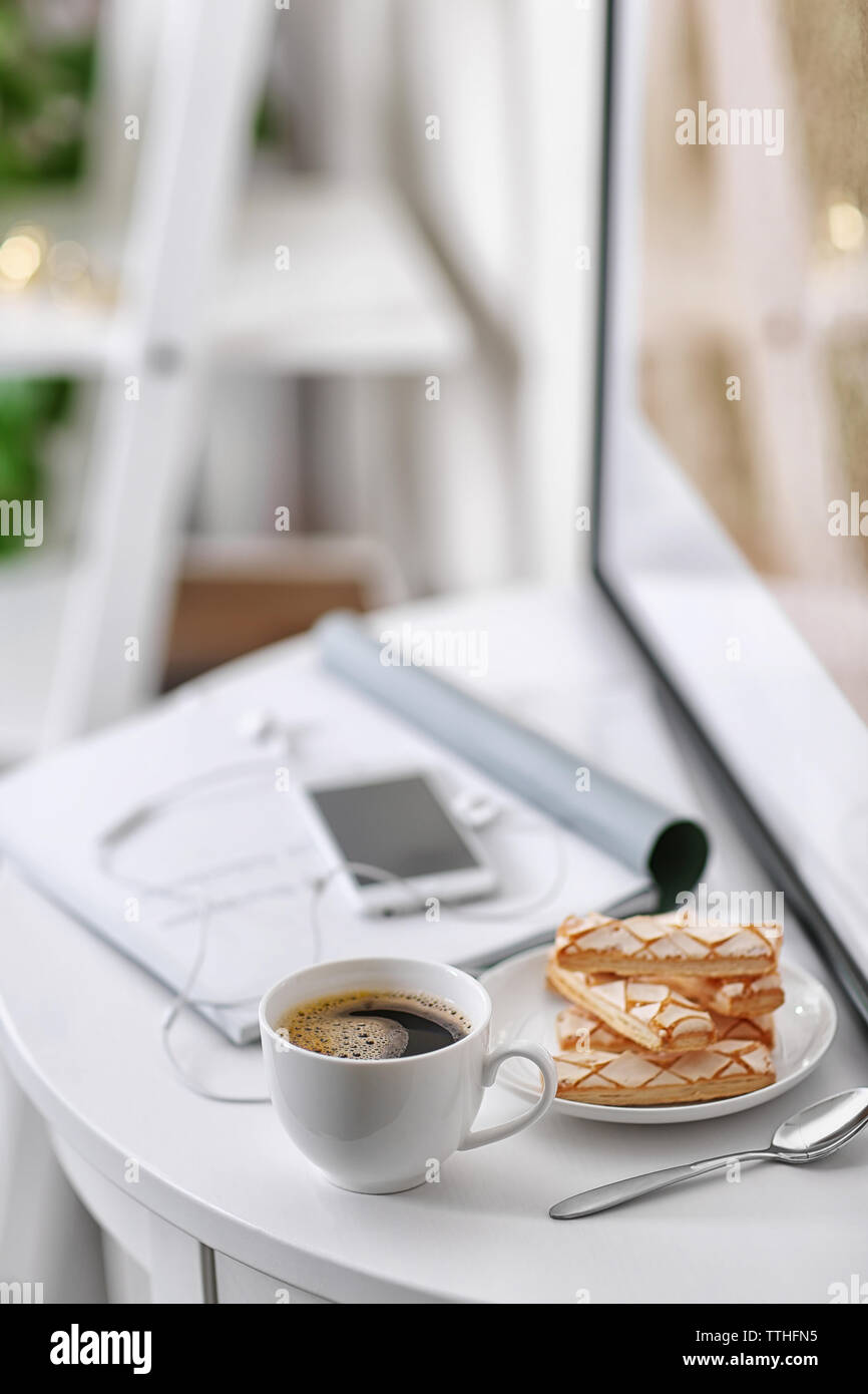 White cup of the coffee and a phone on the table  in a light room.. - Stock Image