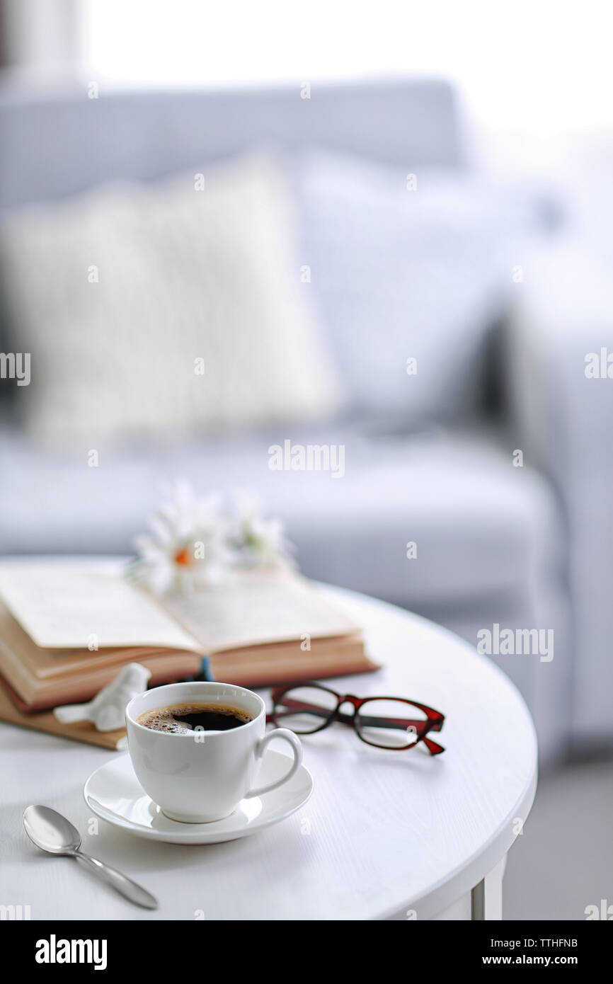 White cup of the coffee and a book on a table  in a light room.. - Stock Image