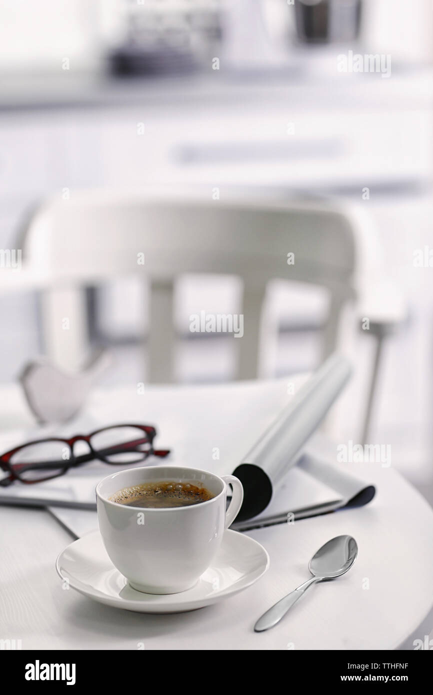 White cup of the coffee on wooden table  in a light room.. - Stock Image