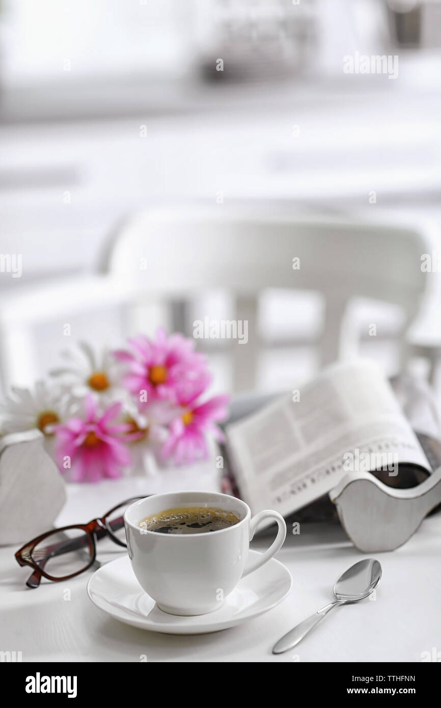 White cup of the coffee and fresh flowers on wooden table in a light room.. - Stock Image