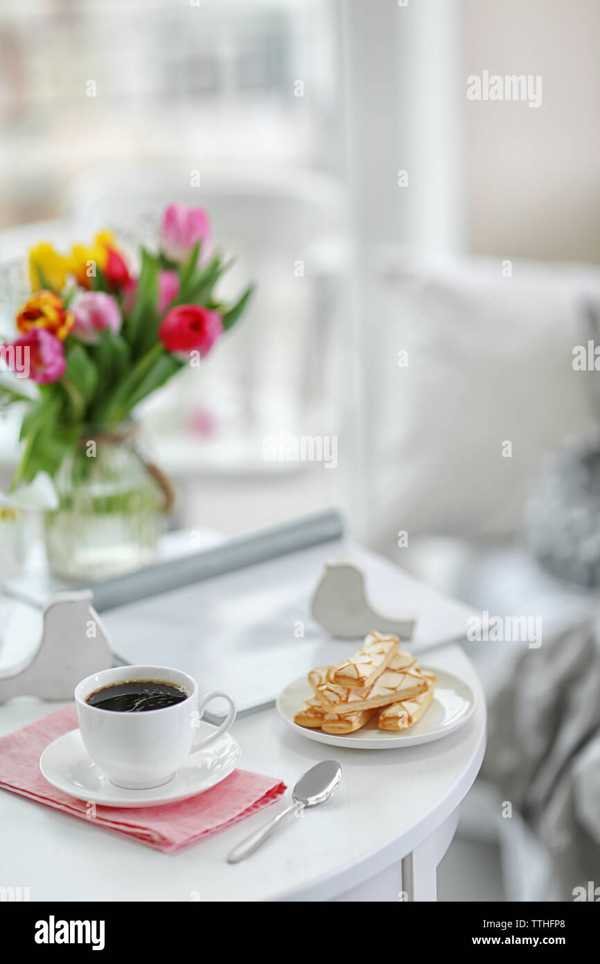 White cup of the coffee and sweets on wooden table  in a light room.. - Stock Image