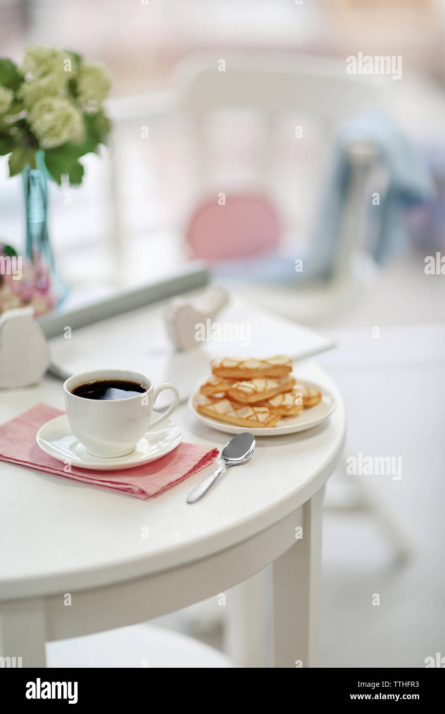 White cup of the coffee and sweets on wooden table  in a light room. - Stock Image