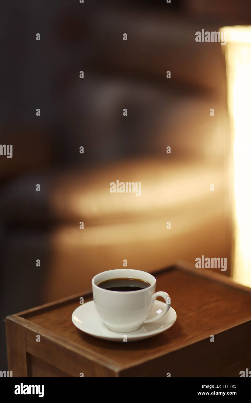White cup of the coffee on a wooden table in a dark room. - Stock Image