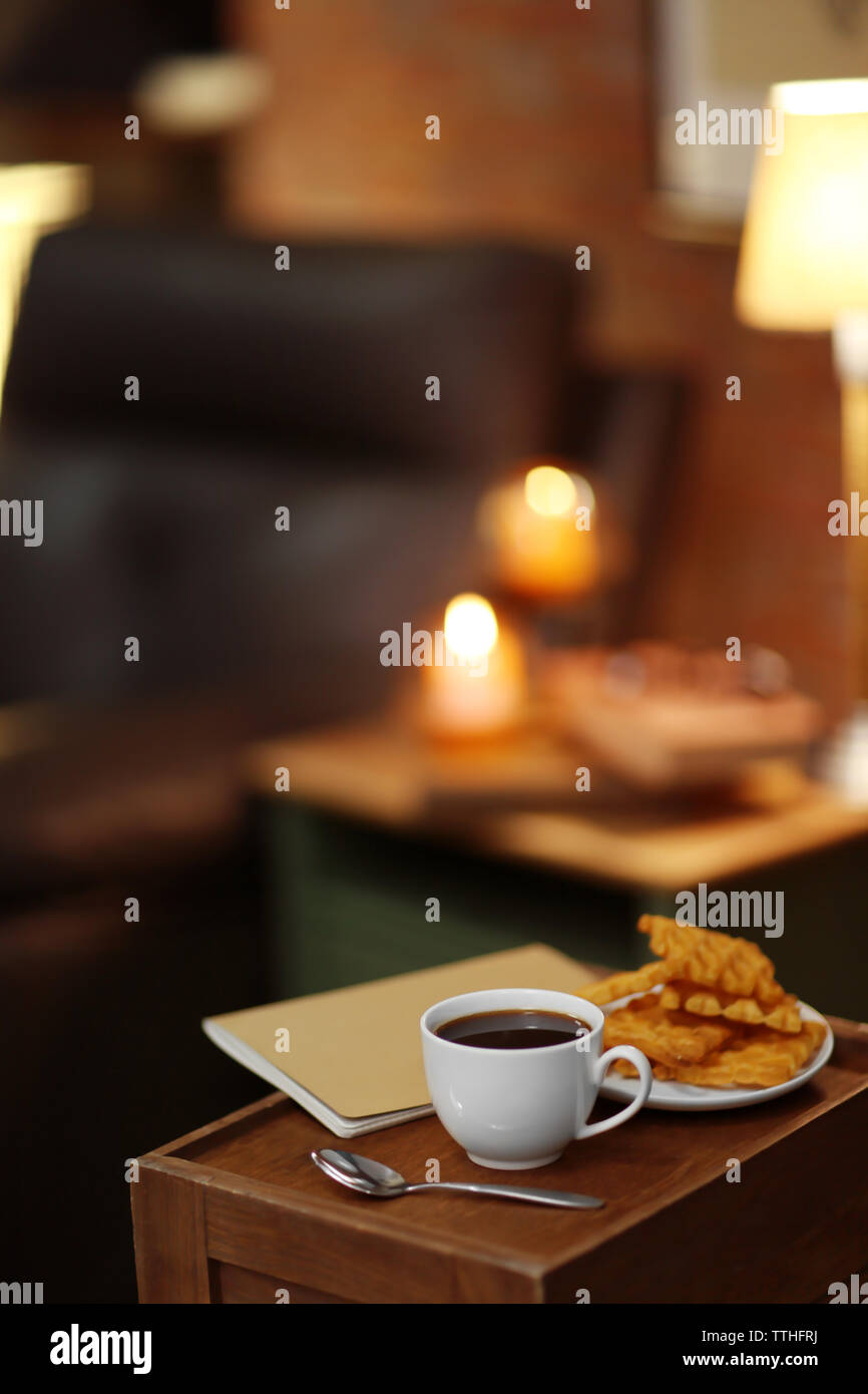White cup of the coffee and biscuits on a wooden table in a dark room.. - Stock Image