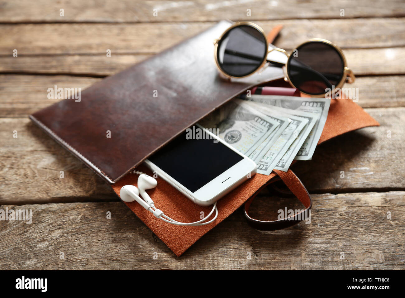 Leather purse with mobile phone, glasses and dollar banknotes on wooden table - Stock Image