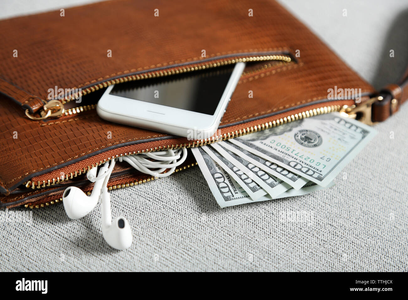 Leather purse with mobile phone and dollar banknotes on grey cloth background - Stock Image