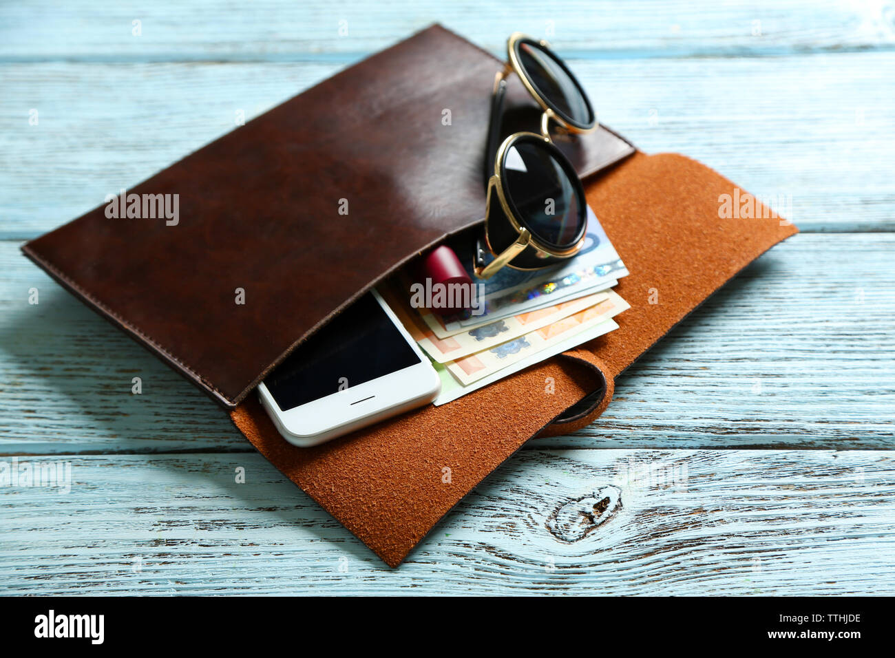 Leather purse with glasses, mobile phone and euro banknotes on wooden background - Stock Image