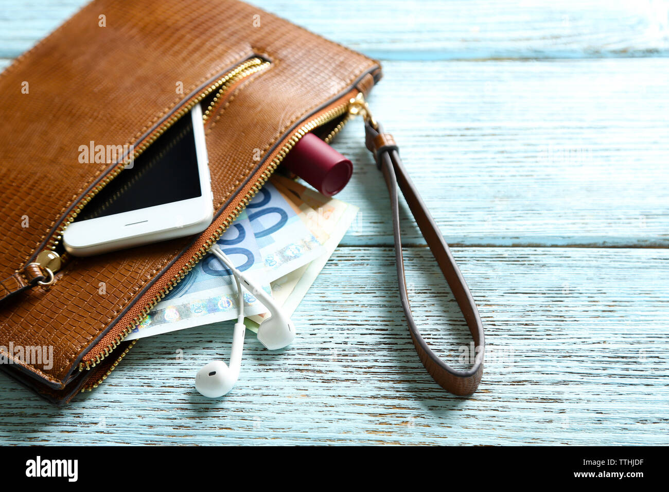 Leather purse with mobile phone and euro banknotes on wooden background - Stock Image