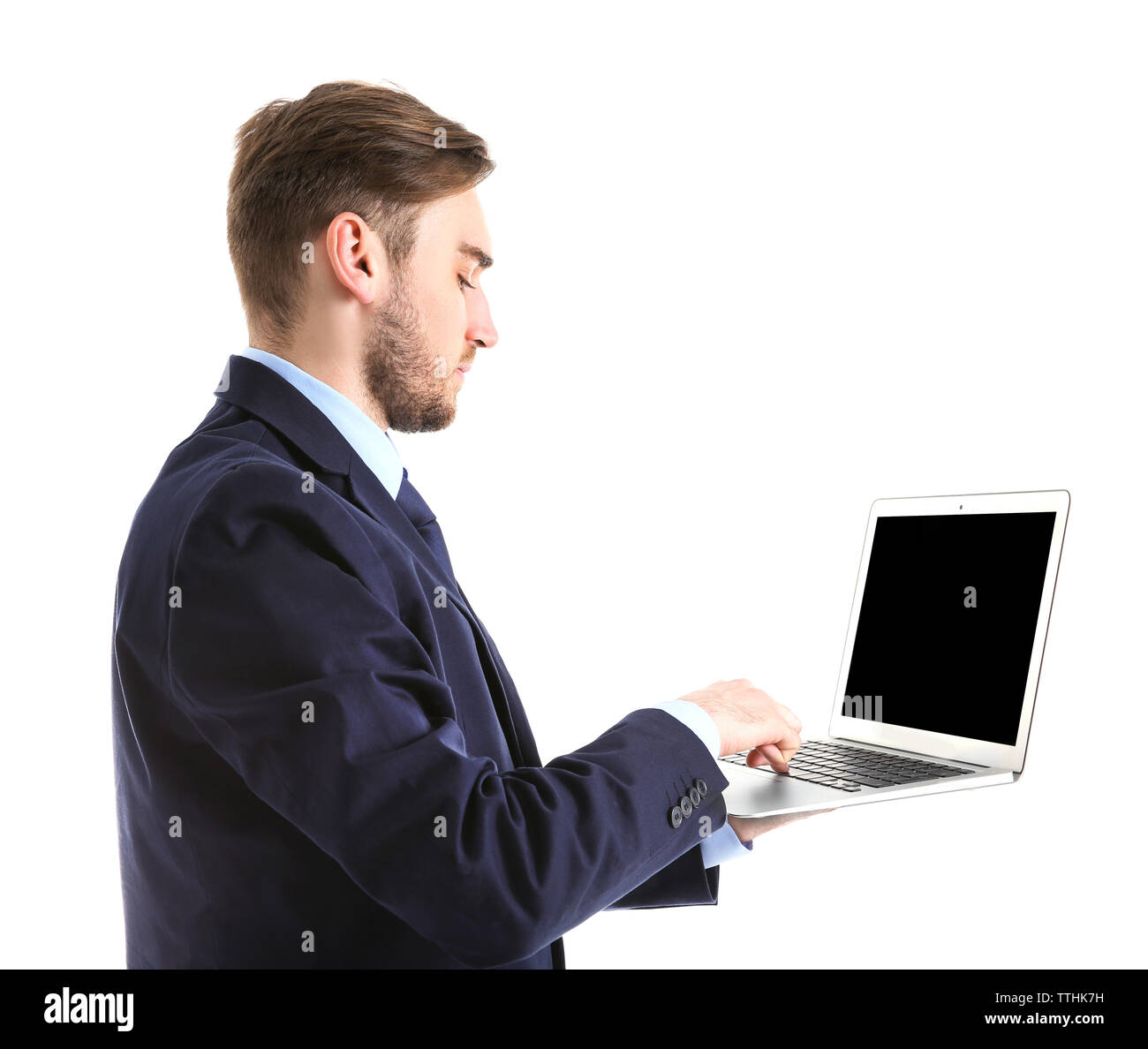 Young man in suit using laptop, isolated on white - Stock Image