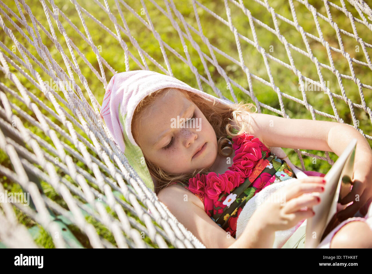 Girl reading book while lying in hammock - Stock Image