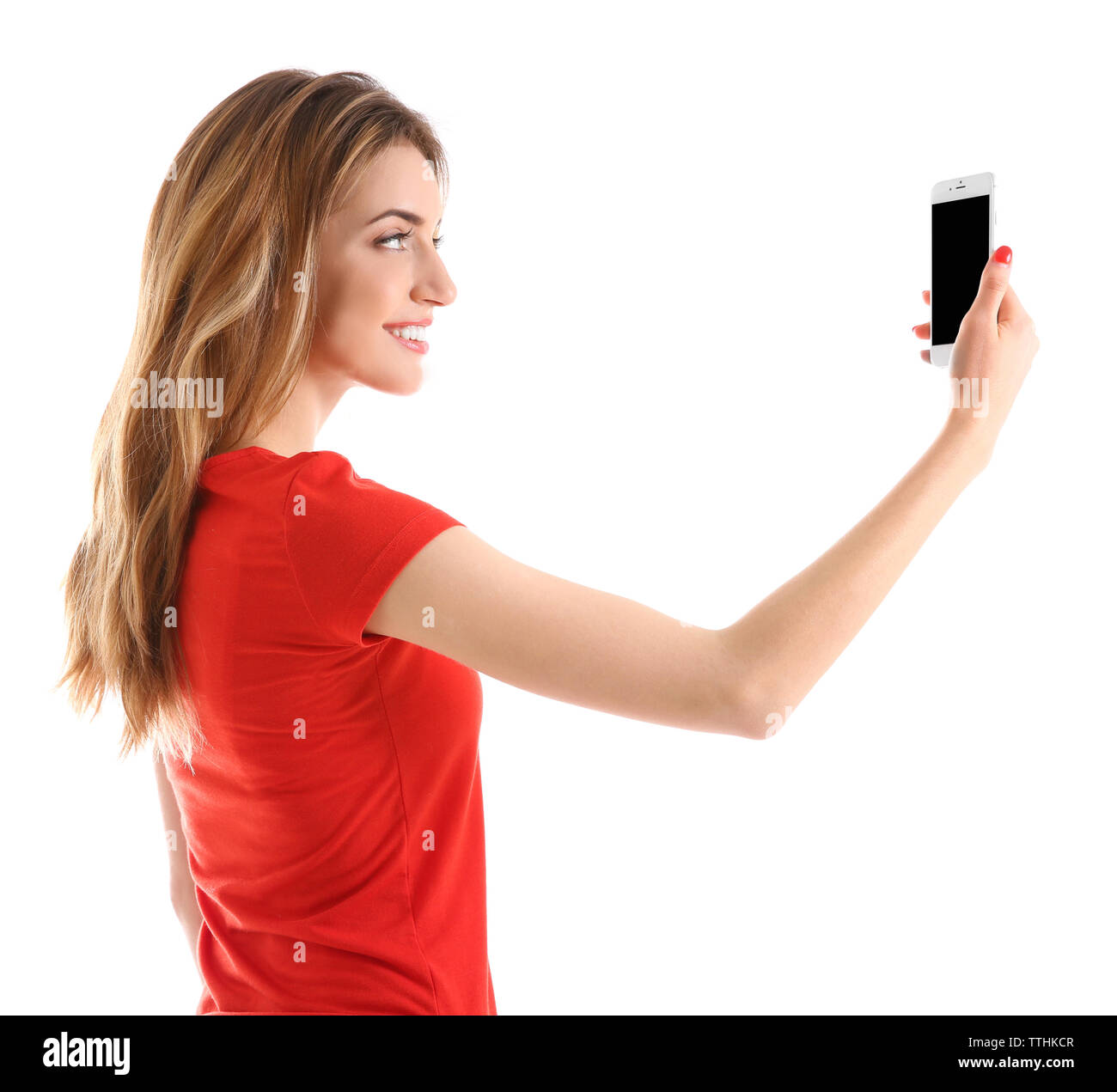 Young woman in red tee-shirt using mobile phone, isolated on white - Stock Image