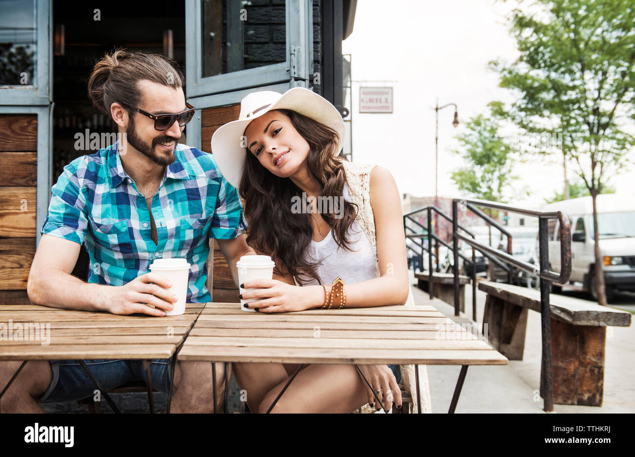 Happy couple holding disposable cups and sitting by table at sidewalk cafe - Stock Image
