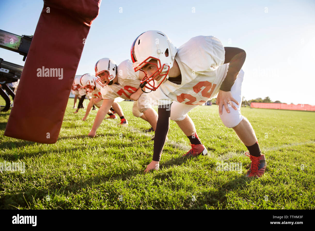 American football players bending by sled at field - Stock Image
