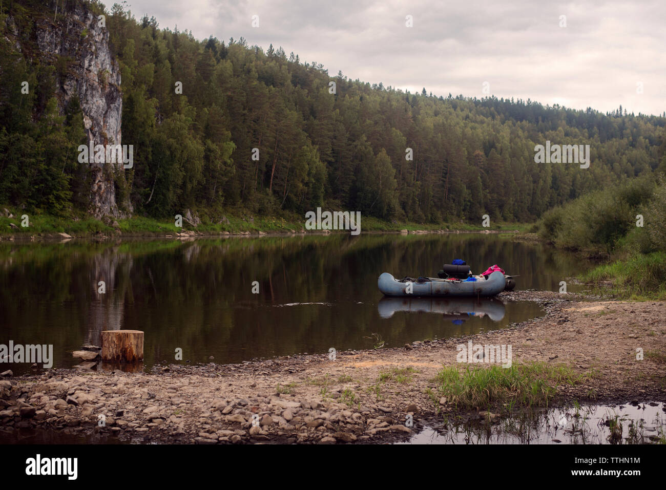 Inflatable raft on riverbank against trees - Stock Image