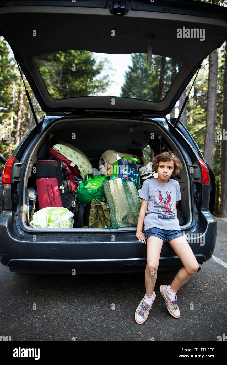 Portrait of girl sitting on car trunk at road - Stock Image