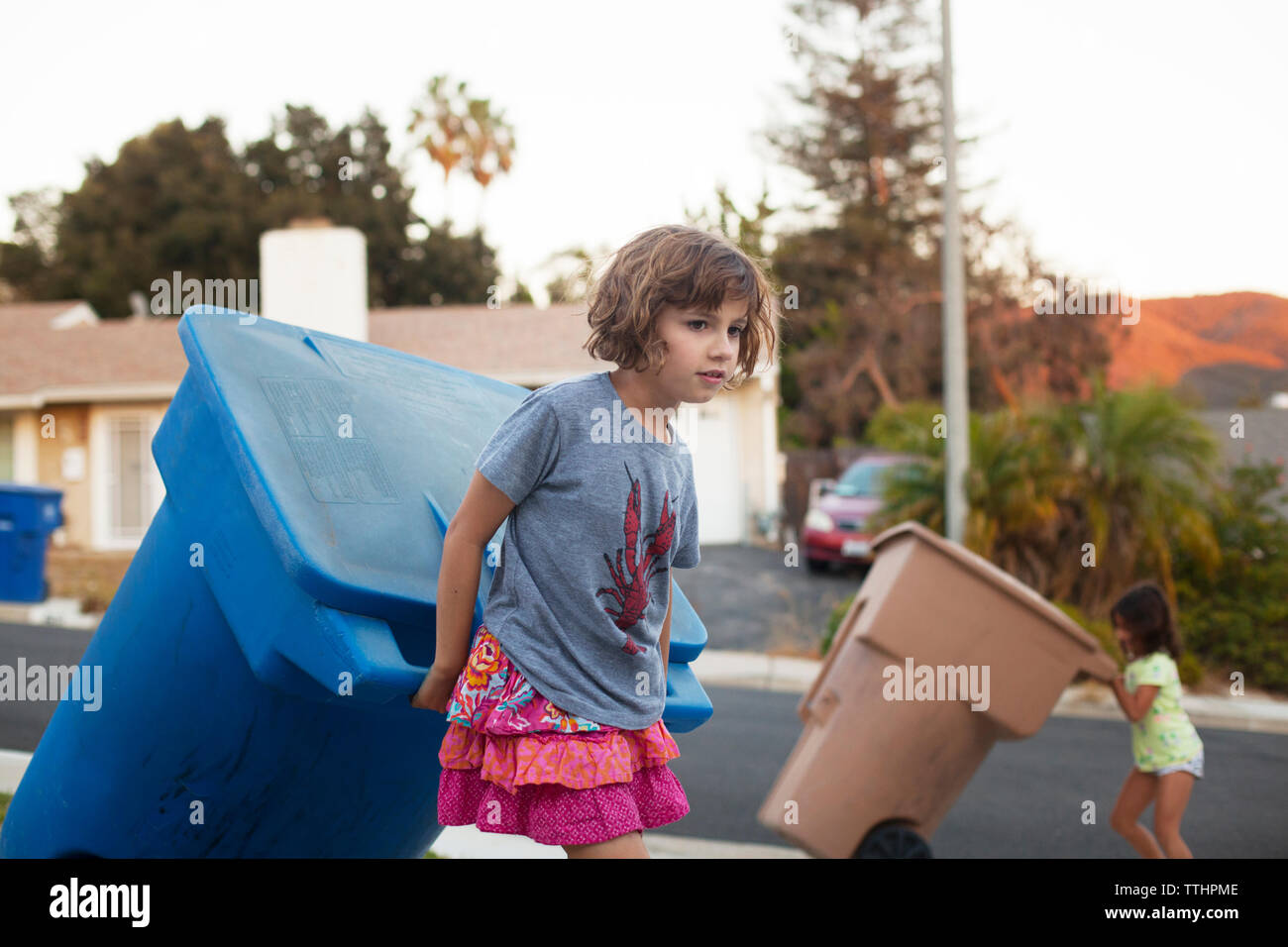 Girl pulling garbage can while walking on road - Stock Image