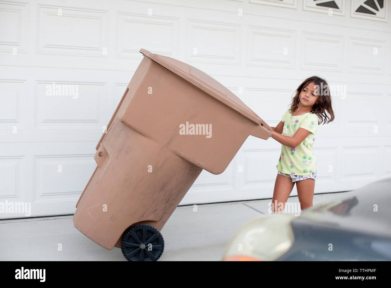 Girl pulling garbage can by wall on sidewalk - Stock Image