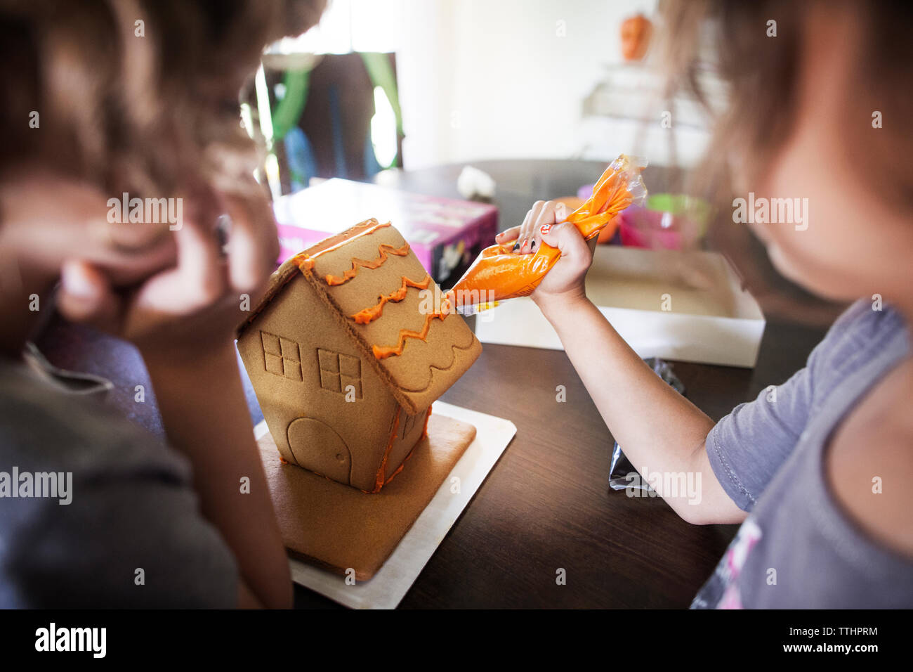 Girls decorating gingerbread house at home - Stock Image