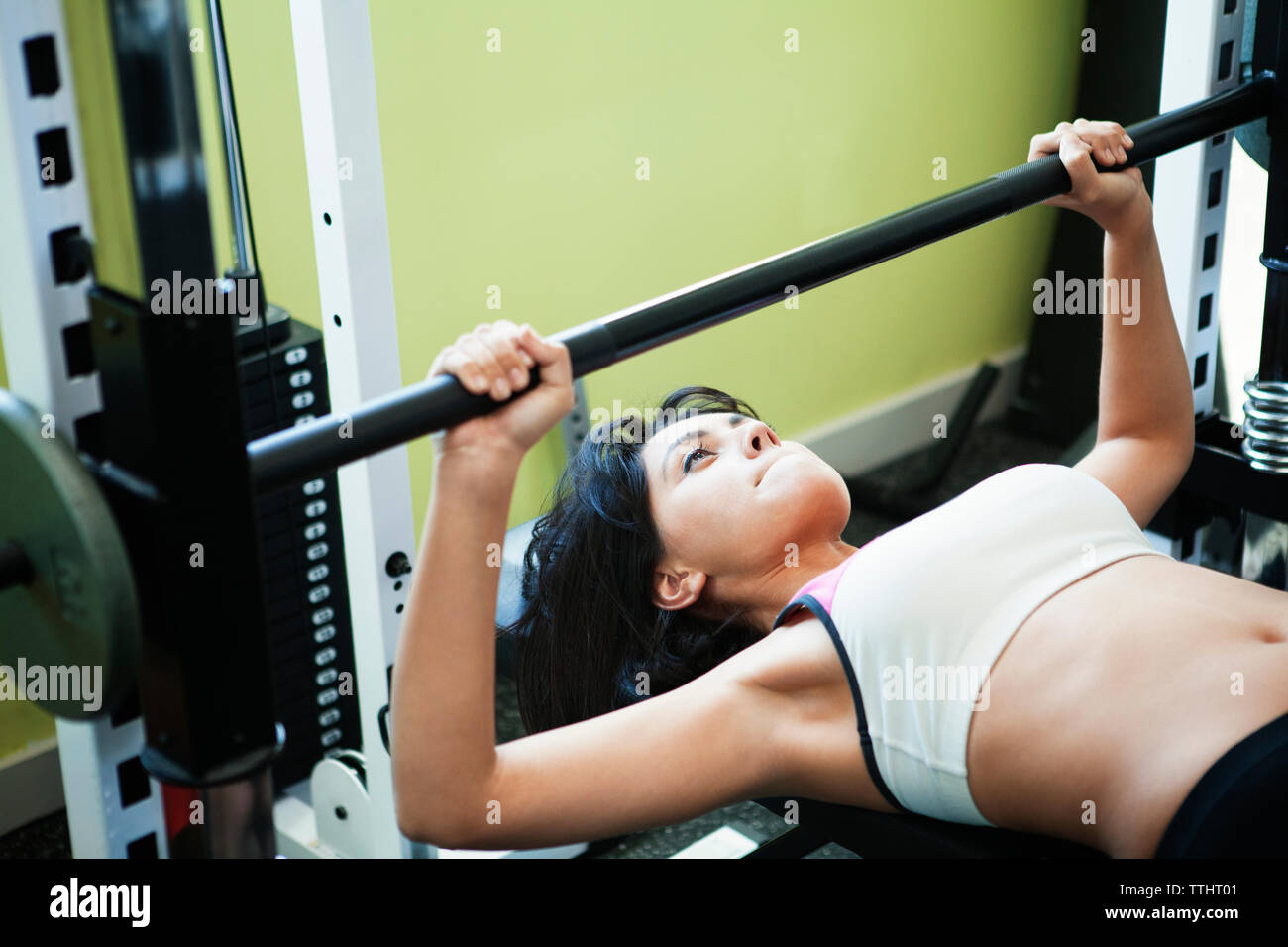 High angle view of woman practicing weights lifting on bench press in gym Stock Photo