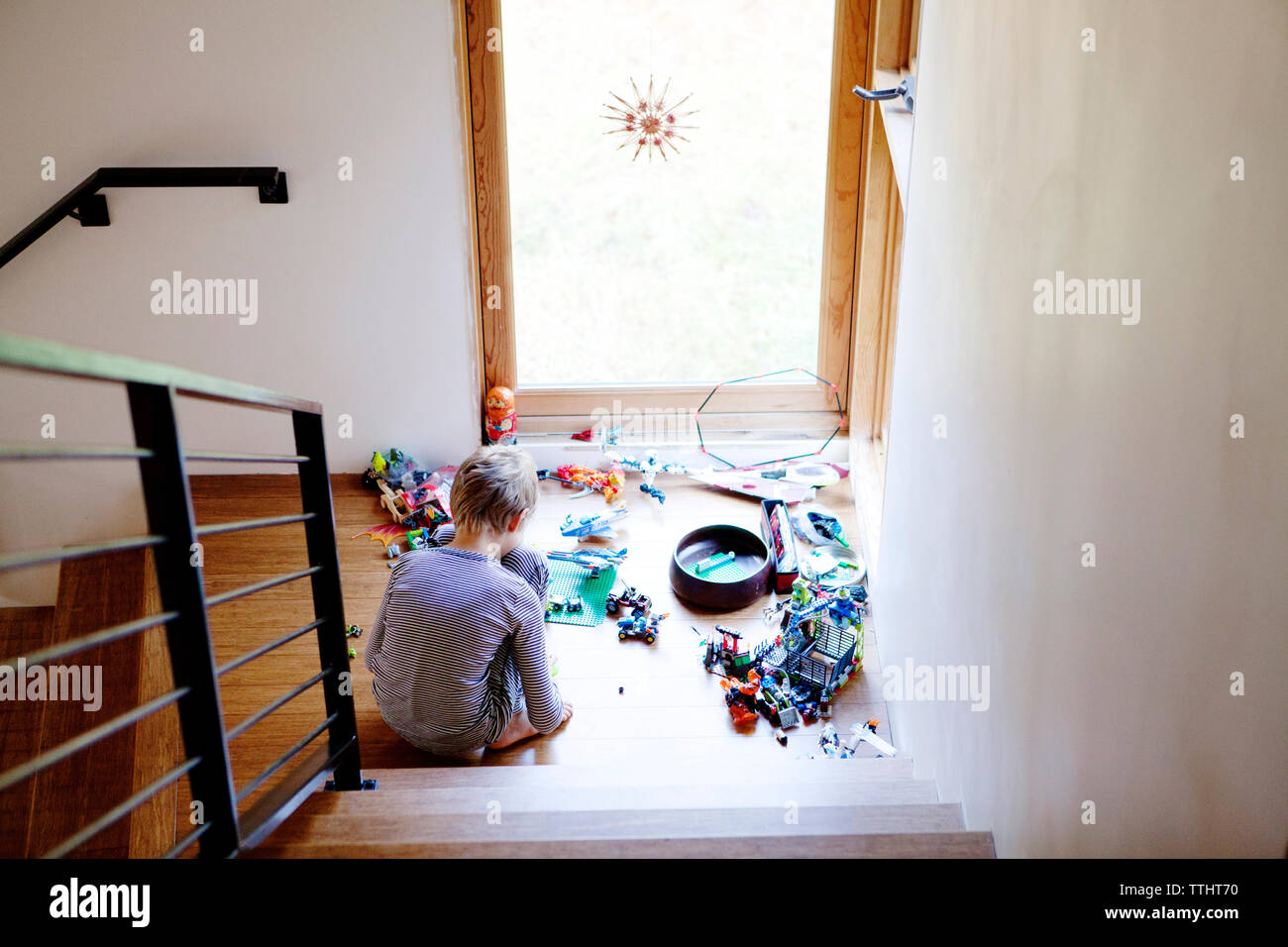 High angle view of boy playing with toys at home - Stock Photo