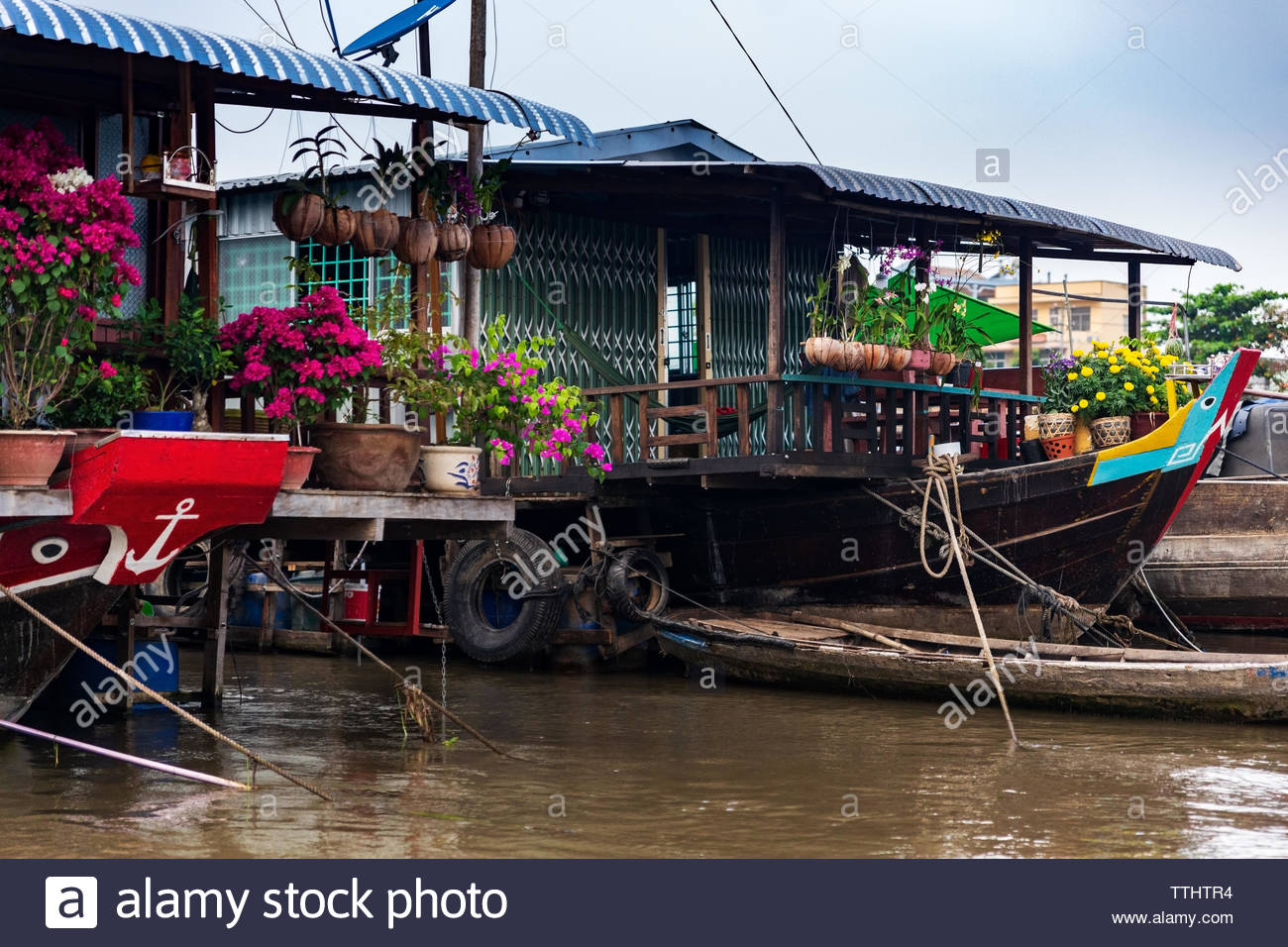 House boats moored together with paper flowers, orchids and yellow flowers for Tet New Year Celebration, Mekong Delta near Can Tho, Vietnam Stock Photo