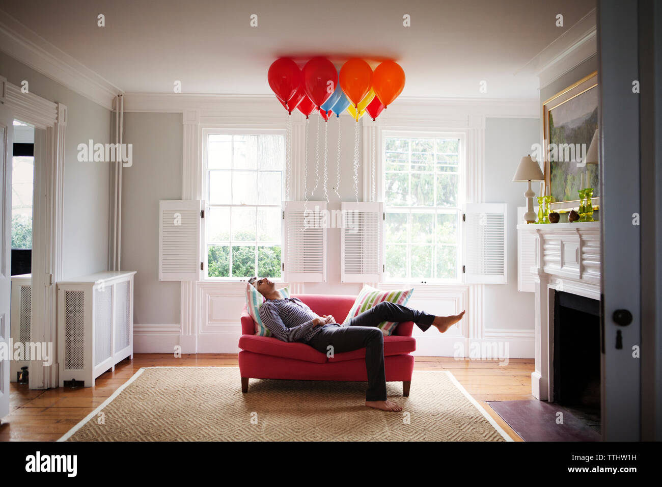 Man looking at helium balloons while lying on sofa - Stock Image
