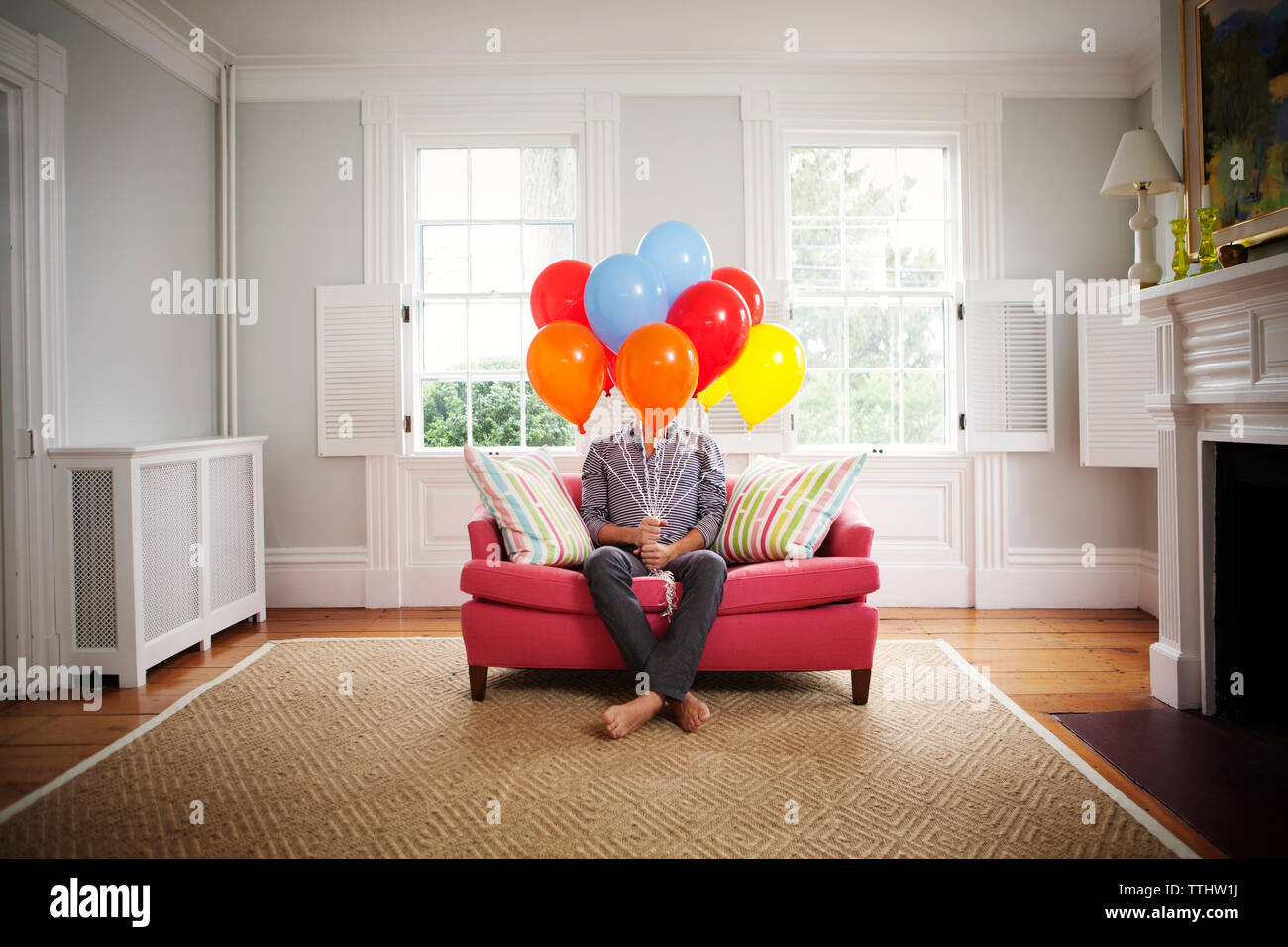 Man holding helium balloons while sitting on sofa at home - Stock Image