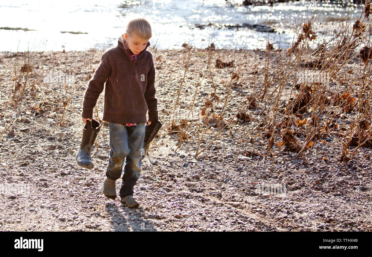 Boy carrying rubber boot while walking on field by river Stock Photo